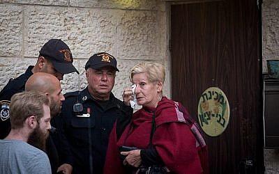 Une femme pleure aux côtés d'agents de police devant l'académie prémilitaire Benny Tzion de Tel Aviv qui avait organisé une randonnée qui a causé la mort de 9 adolescents dans la journée, le 26 avril 2018 (Crédit : Miriam Alster/Flash90)