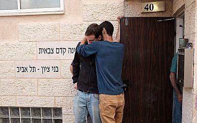 Des gens à l'entrée de l'académie prémilitaire Bnei Tzion de Tel Aviv après la mort de neuf jeunes entraînée par des inondations lors d'une randonnée organisée par l'institution dans le désert de Judée, le 26 avril 2018 (Crédit : Tomar Neudberg/Flash90)