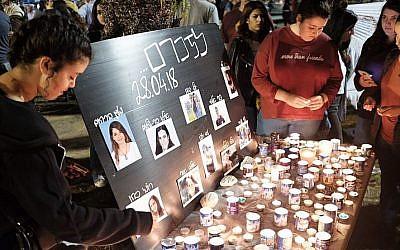 Les gens allument des bougies en mémoire des 10 adolescents israéliens morts lors d'une crue subite survenue dans un lit de rivière dans la région de la mer Morte, sur la place Rabin de Tel Aviv, le 28 avril 2018 (Crédit :Tomer Neuberg/Flash90)