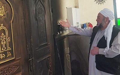 Un imam dans une mosquée du village palestinien d'Aqraba, dans le nord de la Cisjordanie, montre les dégâts causés par un incendie criminel survenu le 13 avril 2018. (Crédit : Zacharia Sadeh / Rabbis for Human Rights)