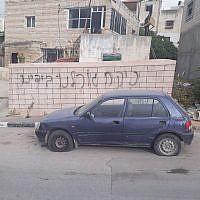Des graffitis découverts sur un mur près d'une voiture dont les pneus ont été lacérés dans le village palestinien de Deir Ammar, près de Qalqilya, le 25 avril 2018 (Crédit : Police d'Israël)