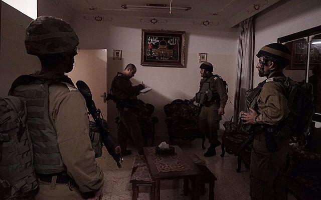 Les soldats israéliens préparent la maison du terroriste palestinien Abd al-Rahman Bani Fadel pour la démolition dans le village d'Aqraba, dans le nord de la Cisjordanie, le 19 mars 2018 (Crédit : Armée israélienne)