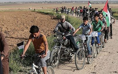 """Des enfants palestiniens font du vélo près de la frontière avec Israël à la périphérie de Khan Younes dans le sud de la bande de Gaza, alors qu'ils participent à une course cycliste exigeant un """"droit au retour"""" en Israël pour des millions de Palestiniens, le 26 mars 2018 (AFP / Said Khatib)"""