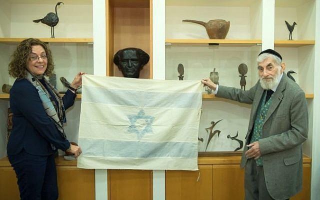 Ezra Gorodesky présente le drapeau israélien cousu par Rebecca Affachiner le 14 mai 1948 à la présidente de l'Université Ben Gurion, la professeur Rivka Carmi (Dani Machlis / Université Ben Gurion)
