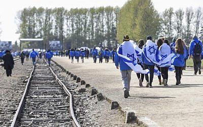 Des participants portant des drapeaux israéliens à l'ancien camp de concentration et d'extermination nazi-allemand Auschwitz-Birkenau lors de la «Marche des vivants» à Oswiecim à Cracovie, en Pologne, le 24 avril 2017 (Crédit : Omar Marques / Agence Anadolu / Getty Images via JTA)