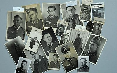Des photos de soldats allemands portés-disparus pendant la Seconde guerre mondiale sur une table de la Croix Rouge allemande, à Munich, dans le sud de l'Allemagne, le 9 avril 2018 (Crédit :   / AFP PHOTO / Christof STACHE / )