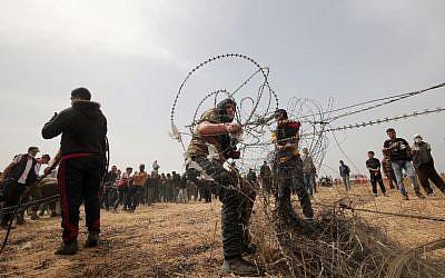 Photo d'illustration. Des Palestiniens arrachent du fil barbelé de la clôture frontalière avec Israël durant les affrontements hebdomadaires du vendredi à Rafah, dans le sud de la bande de Gaza, le 20 avril 2018 (Crédit :  AFP Photo/Said Khatib)