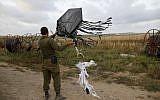 Un soldat israélien tient un cerf-volant lancé par des manifestants palestiniens depuis la frontière du côté de Gaza, transportant une bombe artisanale pour allumer des incendies en Israël, à proximité du kibboutz  Kfar Aza, le 24 avril 2018  (AFP PHOTO / Menahem KAHANA)