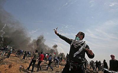 Un manifestant palestinien utilise un lance-pierre pour affronter les forces de sécurité israéliennes près de Khan Younis, dans le sud de la bande de Gaza, le vendredi 27 avril 2018 (Photo AFP / Said Khatib)