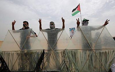 Des émeutiers palestiniens derrière des cerf-volants qu'ils s'apprêtent à faire voler au dessus de la frontière avec Israël, à Khan Younès, le 4 mai 2018 (Crédit : AFP/Said Khatib)