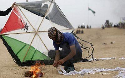 Un Palestinien prépare un dispositif incendiaire attaché à un cerf-volant avant de tenter de le lancer à la clôture frontalière avec Israël, au sud de Jabalia, dans la bande de Gaza, le 4 mai 2018 (Crédit : Mohammed Abed/AFP)