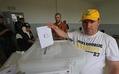 Un partisan libanais du groupe terroriste du  Hezbollah jette son bulletin lors des premières élections législatives depuis 9 ans dans un bureau de vote de la ville majoritairement chiite de Baalbeck,dans l'est de la vallée de Bekaa, à proximité de la frontière avec la Syrie, le 6 mai 2018 (Crédit: AFP PHOTO / Haitham MOUSSAWI)