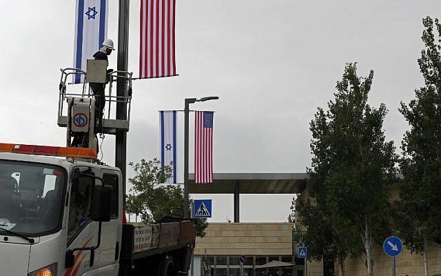 Un ouvrier installe des décorations de drapeaux israéliens et américains devant l'actuel consulat américain à Jérusalem où les autorités américaines installeront la nouvelle ambassade américaine, le 7 mai 2018. Le transfert de l'ambassade de Tel-Aviv à Jérusalem devrait avoir lieu le 14 mai. (AFP / Thomas Coex)
