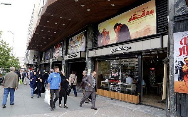 """Des iraniens devant l'affiche du """"Be Vaght-e Cham"""" (""""À l'heure de Damas""""), à Téhéran, le 1 mai 2018. (crédit : AFP/ATTA KENARE)"""