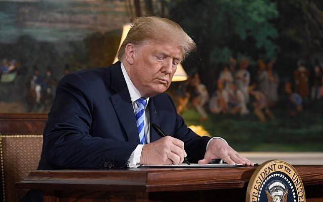 Le président américain Donald Trump signe un document rétablissant les sanctions contre l'Iran après avoir annoncé le retrait américain de l'accord nucléaire iranien, dans la salle d'accueil diplomatique de la Maison Blanche à Washington le 8 mai 2018. (AFP / Saul Loeb)