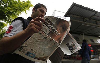 Un Iranien lit son journal au lendemain du retrait des Etats-Unis de l'accord sur le nucléaire décidé par le président Donald Trump (portrait), le 9 mai 2018 (Crédit : / AFP PHOTO / ATTA KENARE)