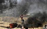 Un émeutier palestinien jette des pierres lors d'affrontements avec les forces israéliennes le long de la frontière avec la bande de Gaza, à l'est de la ville de Gaza, le 11 mai 2018 (Crédit : AFP / MAHMUD HAMS).