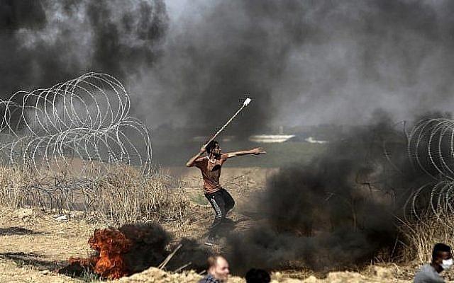 Un manifestant palestinien jette des pierres lors d'affrontements avec les forces israéliennes le long de la frontière avec la bande de Gaza, à l'est de la ville de Gaza, le 11 mai 2018 (AFP PHOTO / MAHMUD HAMS).