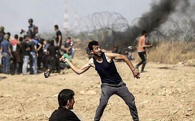 Un manifestant palestinien jette des pierres lors d'affrontements avec les forces israéliennes le long de la frontière avec la bande de Gaza, à l'est de la ville de Gaza, le 11 mai 2018. (AFP PHOTO / MAHMUD HAMS)