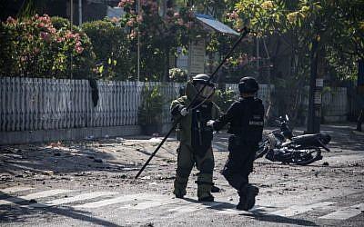 Des membres de la police antiterroriste indonésienne examinent le site d'un attentat-suicide à la bombe aux abords d'une église de Surabaya, le 13 mai 2018 (Crédit :  / AFP PHOTO / JUNI KRISWANTO)