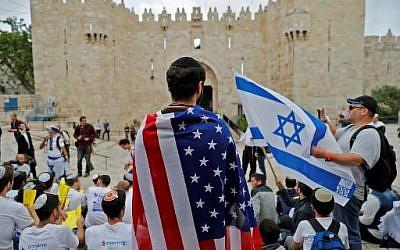 Un Israélien endosse le drapeau américain devant la porte de Damas, dans la Vieille Ville de Jérusalem, le 13 mai 2018. (Crédit : AFP / Ahmad GHARABLI)