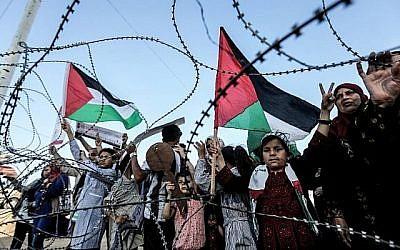 Une fille brandit un drapeau palestinien alors qu'un autre garçon palestinien tient une clé en bois symbolisant le retour, alors qu'ils se tiennent aux côtés d'autres personnes devant le fil barbelé marquant la frontière entre la bande de Gaza et Israël à l'est de la ville de Gaza le 13 mai 2018. (AFP/Mahmud Hams)