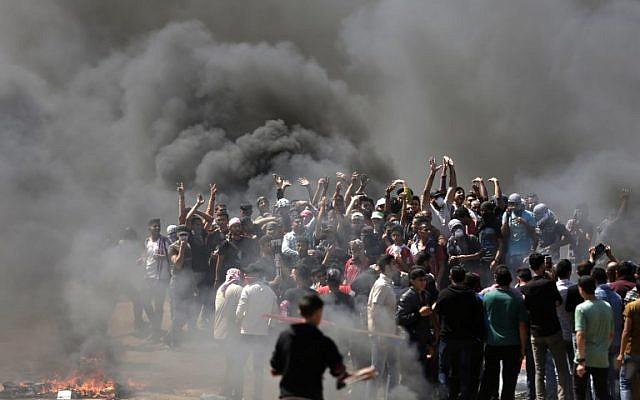 Des émeutiers palestiniens brûlent des peux à la frontière entre Israël et Gaza, à l'est de Gaza City, pour protester contre le transfert de l'ambassade américaine à Jérusalem, le 14 mai 2018. (Crédit : AFP /Mahmud Hams)