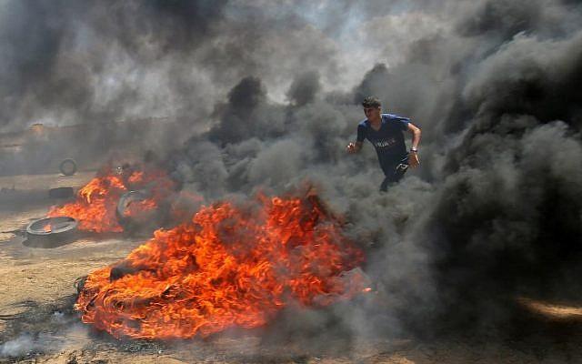 Un Palestinien marche dans la fumée dégagée par des pneus en feu durant des affrontements avec les forces israéliennes le long de la frontière avec la bande de Gaza, à l'est de  Khan Younis, le 14 mai 2018 (Crédit :  AFP PHOTO / SAID KHATIB)