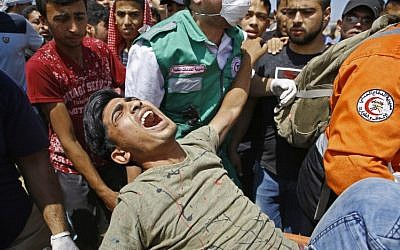 Les services d'urgence et des Palestiniens transportent un manifestant blessé lors d'affrontements avec les forces de sécurité israéliennes près de la frontière entre Israël et la bande de Gaza, à l'est de Jabalia, le 14 mai 2018 (AFP/Mohamed Abed).