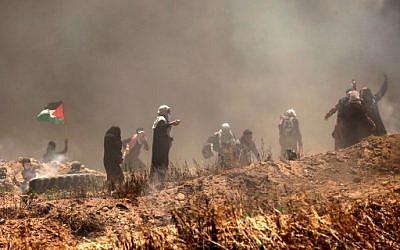 Des manifestants palestiniens lors d'affrontements avec les forces israéliennes près de la frontière entre Gaza et Israël, à l'est de Gaza City, le 14 mai 2018 (Crédit : AFP PHOTO / MAHMUD HAMS)