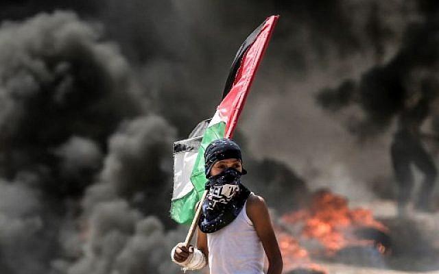 Un jeune garçon brandit un drapeau palestinien pendant les émeutes à la frontière avec Gaza, le 14 mai 2018. (Crédit : MAHMUD HAMS / AFP)