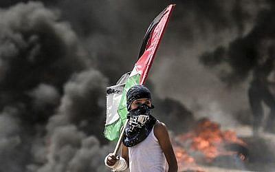 Un Palestinien avec son drapeau national observe les affrontements avec les forces de sécurité israéliennes près de la frontière entre la bande de Gaza et Israël, à l'est de la ville de Gaza, le 14 mai 2018 (AFP PHOTO / MAHMUD HAMS)