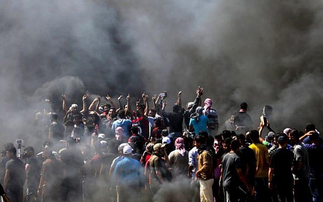 Des Palestiniens crient des slogans lors d'affrontements avec les forces de sécurité israéliennes près de la frontière entre la bande de Gaza et Israël, à l'est de la ville de Gaza, le 14 mai 2018. (MAHMUD HAMS/AFP)
