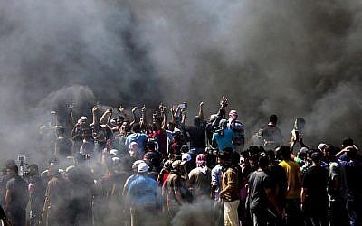Des Palestiniens scandent des slogans lors d'affrontements avec les forces de sécurité israéliennes près de la frontière entre la bande de Gaza et Israël à l'est de la ville de Gaza le 14 mai 2018. (MAHMUD HAMS/AFP)