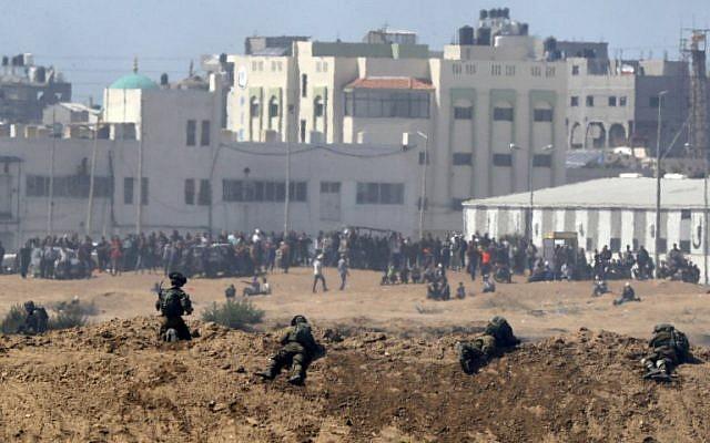 Une photo prise le 14 mai 2018 depuis le kibboutz israélien de Nahal Oz, de l'autre côté de la frontière avec la bande de Gaza, montrant des soldats israéliens qui se tiennent en position et des manifestants palestiniens qui manifestent le long de la frontière avec Israël (AFP / JACK GUEZ)