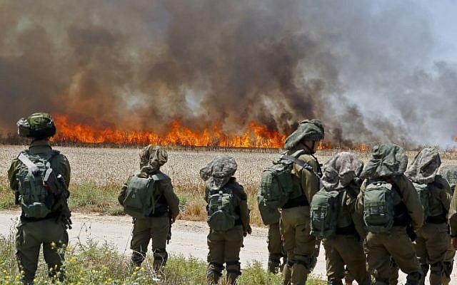 Des soldats israéliens face à un champ de blé en feu près du kibboutz Nahal Oz, incendié  par des cerfs-volants lancés par des émeutiers palestiniens depuis Gaza, le 14 mai 2018. (Crédit : JACK GUEZ/AFP)