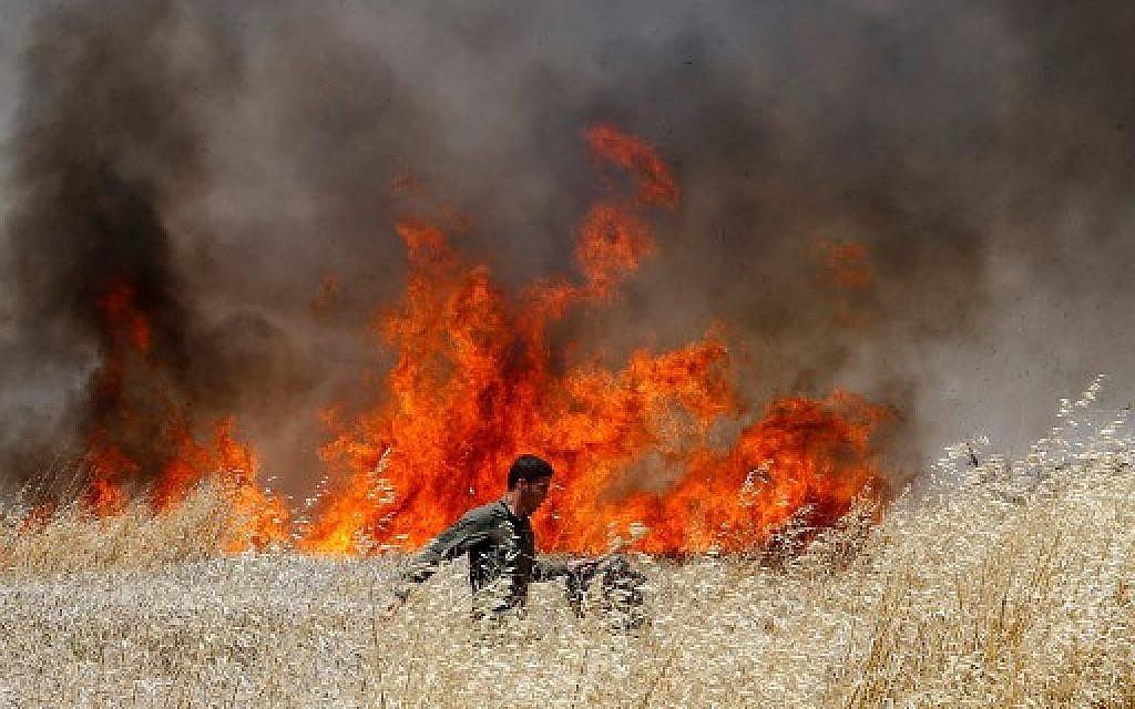 Un soldat israélien tente d'éteindre un feu dans un champ de blé du kibboutz Nahal Oz, incendié par des cerfs-volants envoyés depuis Gaza par des émeutiers, le 14 mai 2018. (Crédit : AFP / JACK GUEZ)