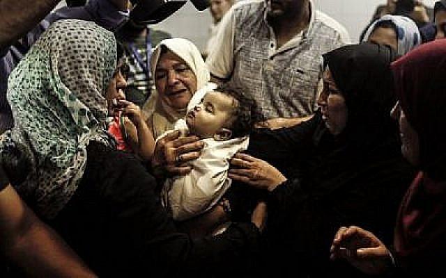 Des proches de Leila al-Ghandour, un bébé palestinien de 8 mois qui, selon le ministère de la Santé de Gaza, dirigé par le Hamas, est mort par inhalation de gaz lacrymogène lors des affrontements dans l'est de Gaza la veille, la gardent à la morgue de l'hôpital al-Shifa dans la ville de Gaza le 15 mai 2018. Un médecin de Gaza, qui a indiqué qu'elle avait des problèmes de santé préexistants, et Israël ont contesté les circonstances de sa mort. (AFP/Mahmud Hams)