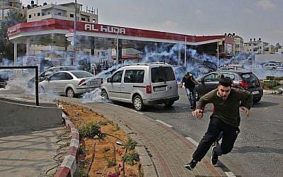 Des Palestiniens fuient les gaz lacrymogènes lancés par les forces israéliennes durant une manifestation à Ramallah, en Cisjordanie, le 15 mai 2018 (Crédit : AFP/ABBAS MOMANI)