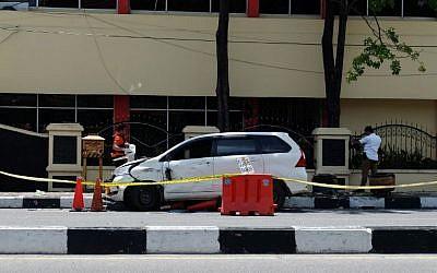 Des policiers indonésiens examinent la voiture utilisée par les terroristes devant le siège de la police à Pekanbaru, à Riau , après l'attentat commis le 16 mai 2018 (Crédit : AFP PHOTO / DEDY SUTISNA