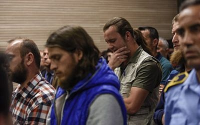 Besart Peci, à droite, un extrémiste musulman condamné pour avoir planifié un attentat contre la sélection de football israélienne, fait un geste aux côtés de ses complices devant un tribunal de Pristina, au Kosovo, le 18 mai 2018  (Crédit : / AFP PHOTO / Armend NIMANI)