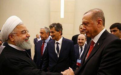 Le président turc Tayyip Erdogan, à droite, serre la main avec son homologue iranien Hassan Rouhani durant une réunion extraordinaire de l'Organisation de la coopération islamique à Istanbul, le 18 mai 2018 (Crédit : AFP PHOTO / POOL / Kayhan OZER)