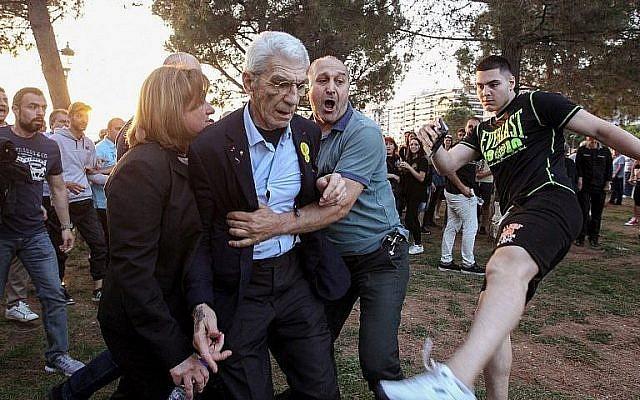 Le maire de la deuxième ville de Grèce - Thessalonique - Yiannis Boutaris, au centre, après avoir été agressé par des membres présumés d'extrême-droite au sein de sa municipalité, le 19 mai 2018 (Crédit : AFP/Eurokinissi/Eurokinissi)