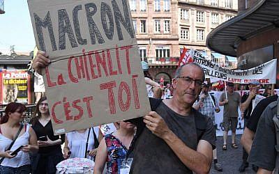 Un homme brandit une pancarte anti-Macron pendant un rassemblement organisé par un collectif d'organisations de gauche et d'extrême-gauche, à Strasbourg, le 26 mai 2018. (Crédit : AFP / PATRICK HERTZOG)