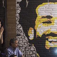 Un homme réagit en regardant le match final de la Ligue des champions UEFA entre le Real Madrid et Liverpool, dans un coffee shop du Caire, en Egypte. Au mur, un portrait de Mohamed Salah, avant de l'équipe de Liverpool, le 26 mai 2018 (Crédit : / AFP PHOTO / KHALED DESOUKI