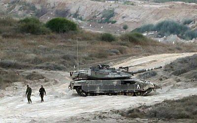 Des soldats israéliens marchent près d'un char de l'armée patrouillant le long de la frontière entre Israël et la bande de Gaza le 29 mai 2018. (AFP PHOTO / Jack GUEZ)