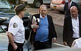 Harvey Weinstein se livre à la police de New York en vue d'une probable inculpation, sept mois après des accusations de viol et de harcèlement, le 25 mai 2018. (Crédit : Kevin Hagen/Getty Images/AFP)