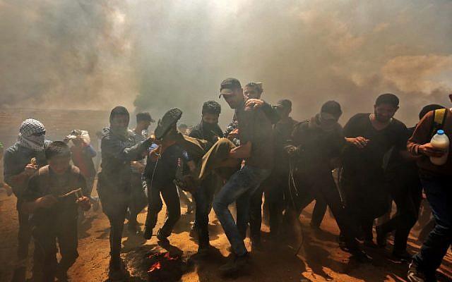 Des Palestiniens transportent un manifestant blessé lors d'affrontements avec les forces israéliennes à proximité de la frontière entre la bande de Gaza et Israël à l'est de la ville de Gaza, le 14 mai 2018 (MAHMUD HAMS / AFP)
