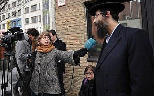 Aron Berger interviewé par un journaliste belge devant l'école de sa fille, Anvers, en août 2013. (Crédit : Cnaan Liphshiz/JTA)