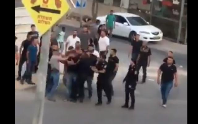Capture d'écran d'une vidéo qui semble montrer un agent de police giflant un suspect arrêté au visage durant des confrontations violentes entre la police et les résidents de la ville de Rahat, au sud du pays, le 25 mai 2018 (Capture d'écran :   Twitter)